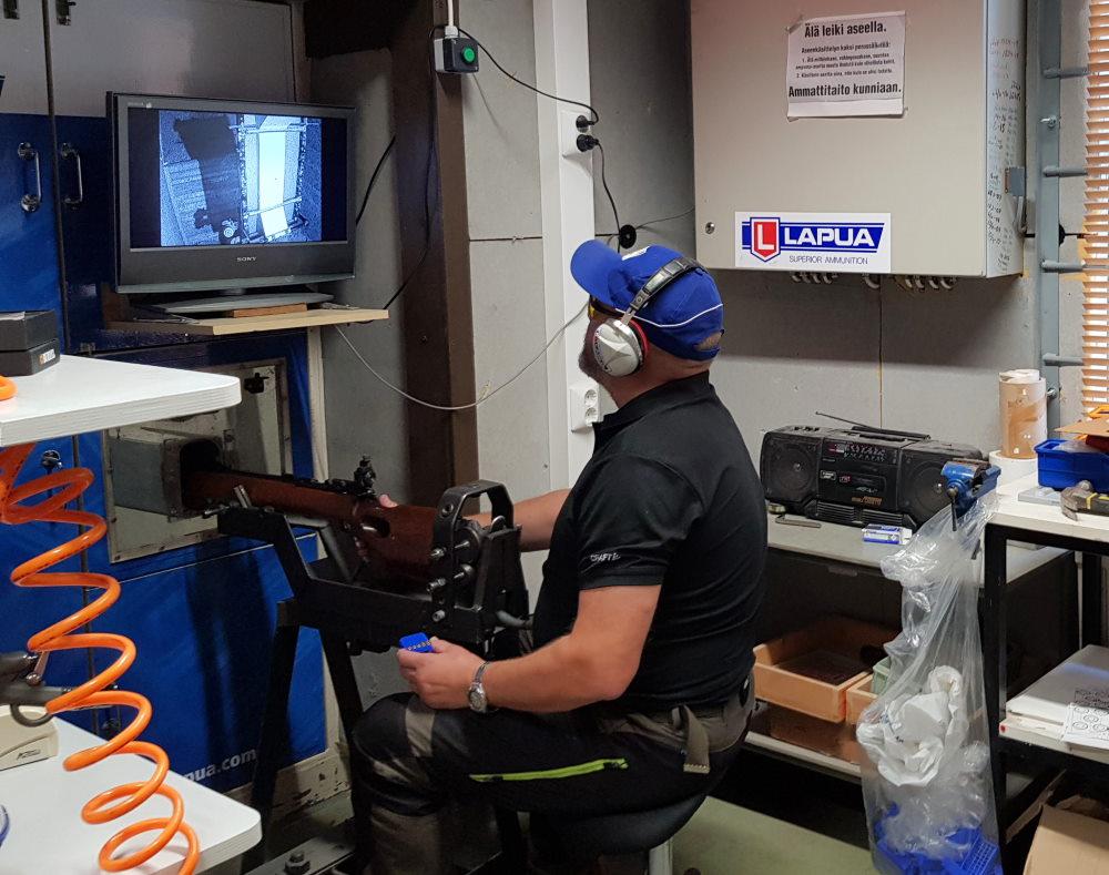 Olli testaa kiväärin käyntiä erilaisilla patruunoilla. Osumia tarkastellaan monitorin kautta.